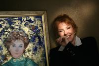 Lisa Donovan stands with her portrait, by Edna Hibel